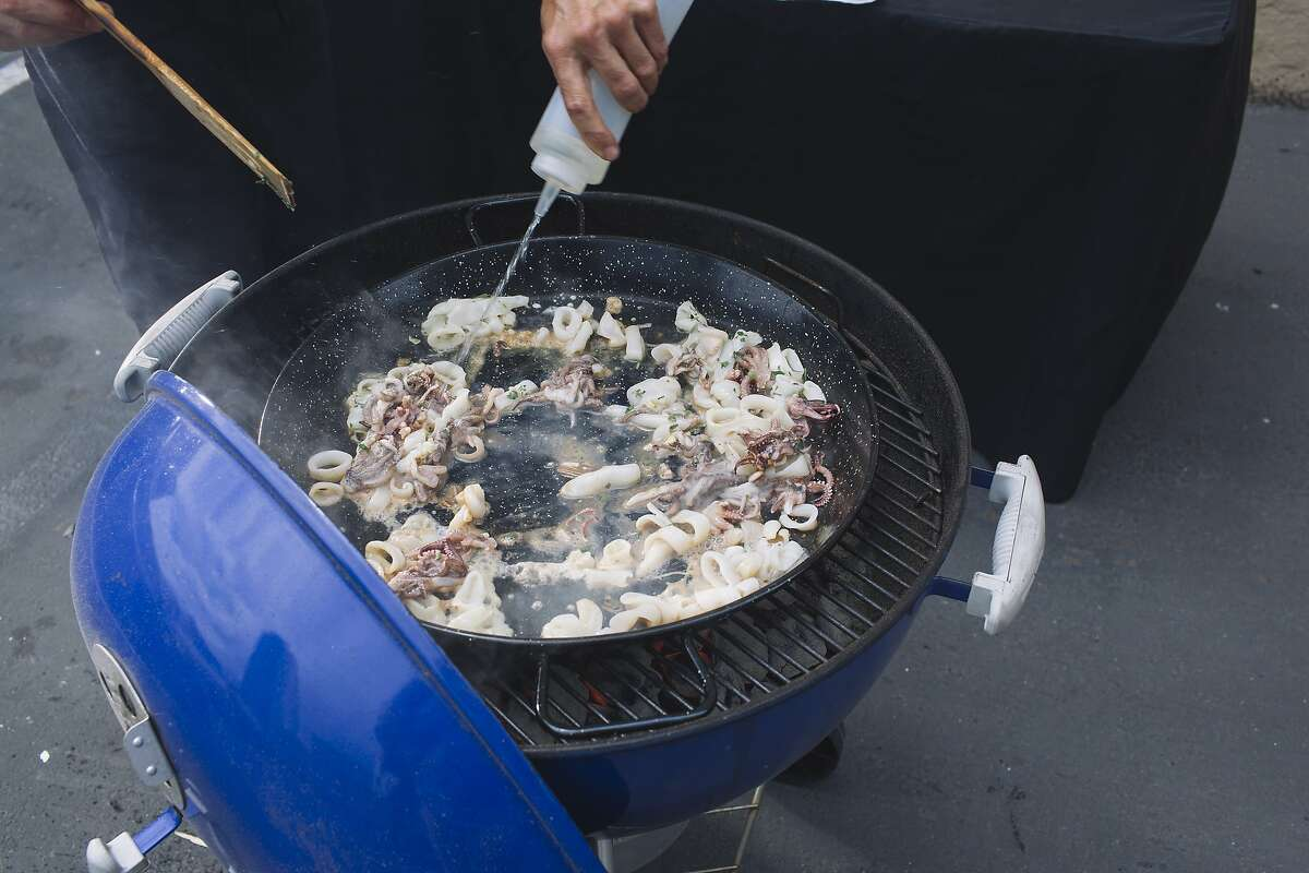 Eduardo Balaguer of Venga Paella cooks calamari over a charcoal grill during a paella cooking demonstration at the San Francisco Chronicle office in San Francisco, Calif. on Monday, July 7, 2014.
