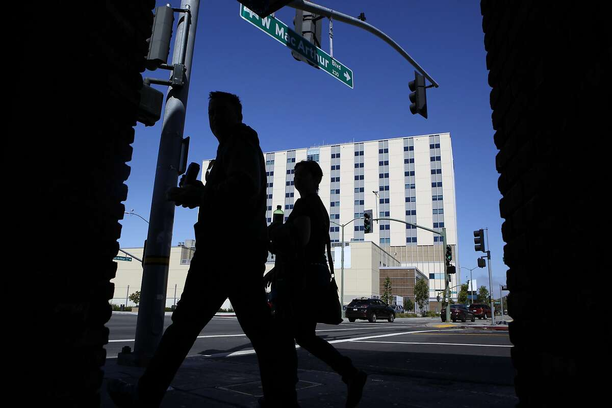 People walk past the new Kaiser Permanente Oakland Medical Center located at 3600 Broadway in Oakland, CA, Saturday, July 5, 2014.