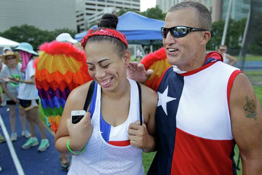 "Amanda DeJesus, left, and Pete Dodd both of Houston joke together during the Transplant Games at Rice University Monday, July 14, 2014, in Houston. Both are heart transplant recipients. She is wearing a set of wings her family gave her. She credits Dodd's track coaching for her success in the games. She said, ""He did and excellent job training me and preparing me for these games. He helped me focus and get out of my head."" Photo: Melissa Phillip, Houston Chronicle / © 2014  Houston Chronicle"