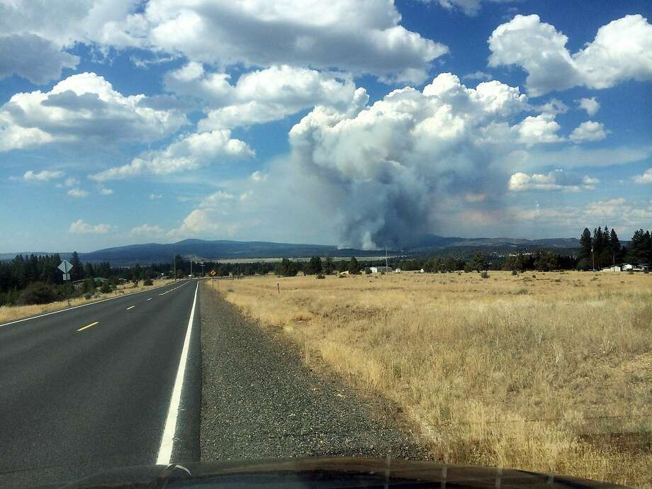In this photo provided by South Central Oregon Fire Management Partnership, smoke from a fire is seen Sunday, July 13, 2014, near Moccasin Hill, Ore. Officials say a fast-growing wildfire in southern Oregon has destroyed homes and forced dozens of evacuations.  Photo: Associated Press