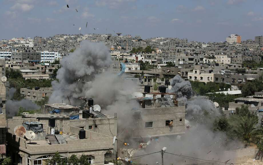 Smoke and debris rise from an Israeli missile strike that hit a building in Jabalya refugee camp in the Gaza Strip. The death toll in Gaza from the air strikes is at least 185, with more than 1,000 wounded. Photo: Hatem Moussa, Associated Press