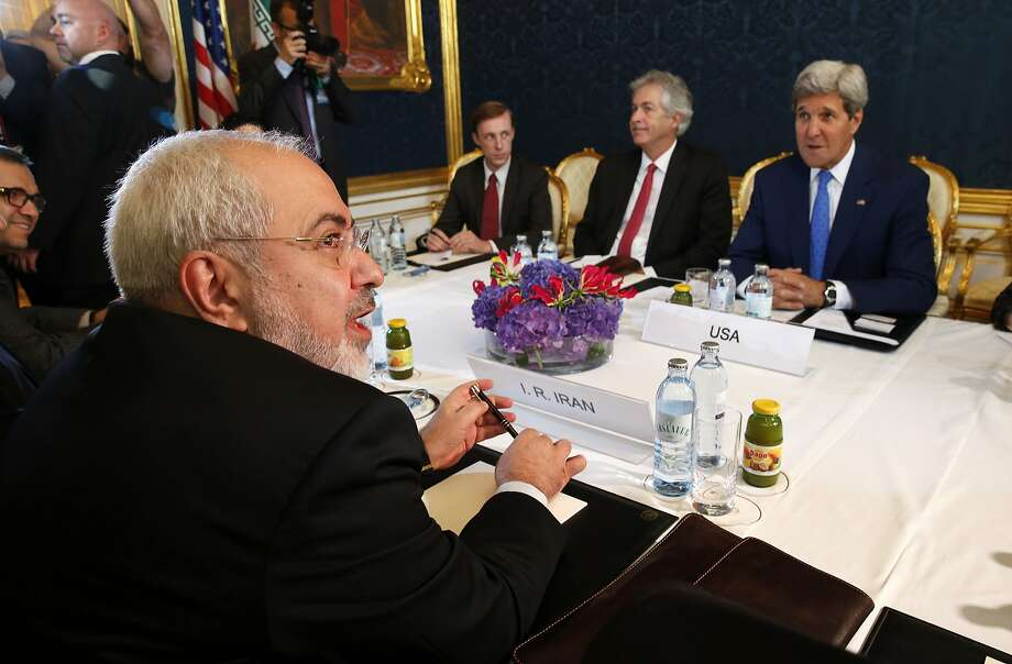 "Iran's Foreign Minister Javad Zarif (L) holds a bilateral meeting with US Secretary of State John Kerry (R) on the second straight day of talks over Tehran's nuclear program in Vienna, on July 14, 2014. US Secretary of State John Kerry pressed his Iranian counterpart Monday to make ""critical choices"", six days before a deadline to cut a historic deal that would finally dispel fears about Tehran's nuclear drive. AFP PHOTO/ POOL / JIM BOURGJIM BOURG/AFP/Getty Images Photo: Jim Bourg, AFP/Getty Images"
