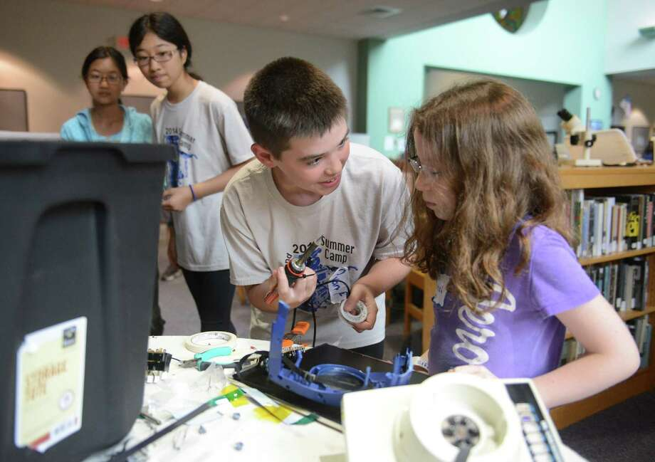 Camp mentor Ryan Fitzgerald, center, 12, of New Milford, teaches Hannah Elfenbein, 8, of Brookfield, how to use a soldering iron during the Robotics and Beyond Summer Camp at New Milford High School in New Milford, Conn. Monday, July 14, 2014.  The camp, now in its 11th year, is separated into four week-long sessions for kids ages five to 17 that provide a hands-on opportunity to learn STEM- and design-based projects for all ages and ability levels.  Some projects the kids are working on include Lego NXT robots, modular oragami, graphic design, engineering design, animation and programming. Photo: Tyler Sizemore / The News-Times