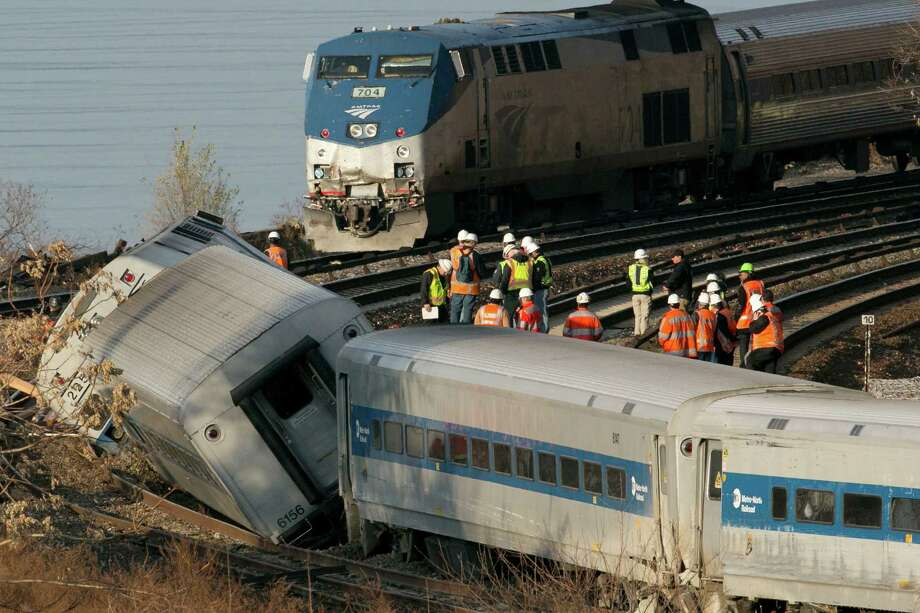 In this Dec. 1, 2013 file photo, an Amtrak train, top, traveling on an unaffected track, passes a derailed Metro North commuter train in the Bronx borough of New York. Photo: Mark Lennihan, AP File/Mark Lennihan / Associated Press