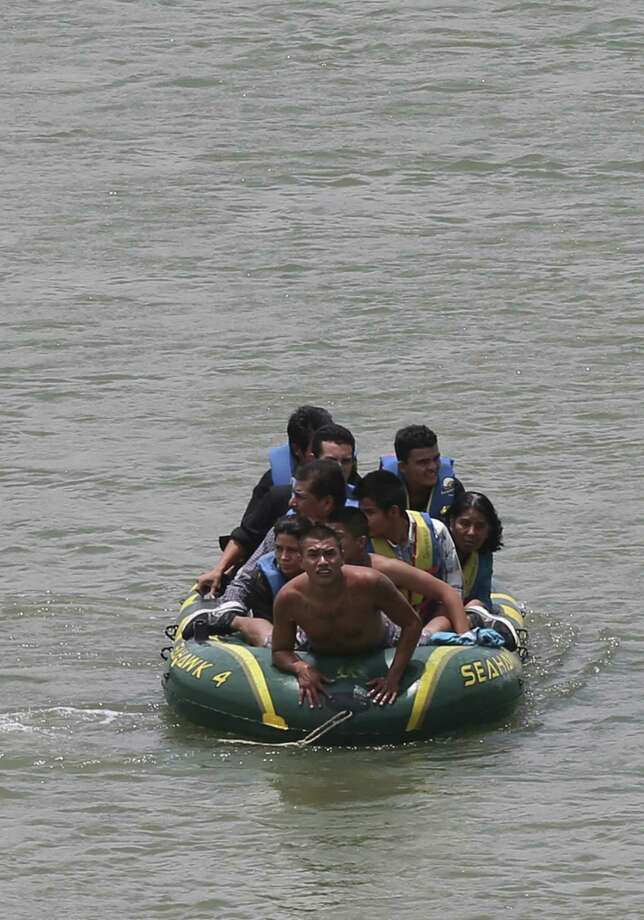 Smugglers carry immigrants across the Rio Grande in Roma. A reader says people who believe the U.S. should accept the immigrants should take them into their homes. Photo: Jerry Lara / San Antonio Express-News / ©2014 San Antonio Express-News