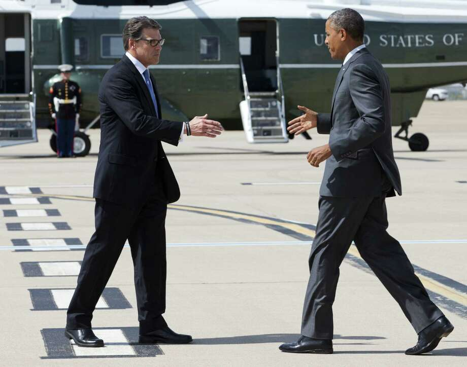 President Barack Obama is greeted by Gov. Rick Perry as he  arrives in Dallas for talks on immigration. From the safety of Dallas, both were free to take political stances about the border situation. Photo: Jacquelyn Martin / Associated Press / AP