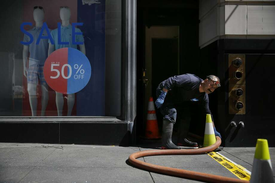 A worker with Ideal Restoration adjusts hoses removing water from the Lacoste store on Geary Street. Photo: Lea Suzuki, The Chronicle
