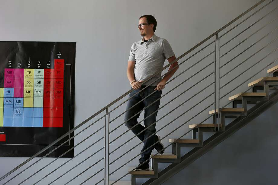 Steve Newcomb pauses on a staircase in his Famo.us offices near a poster that shows the staff structure of the San Francisco company, which helps programmers. Photo: Brant Ward, San Francisco Chronicle