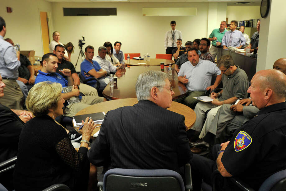 Mayor David Martin, center foreground, presides over a meeting of public safety officials and local business owners at the Downtown Special Services District offices at Landmark Square in Stamford, Conn., on Monday, July 14, 2014. The meeting was held in response to the shooting in Columbus Park early Sunday morning that injured five people. Photo: Jason Rearick / Stamford Advocate