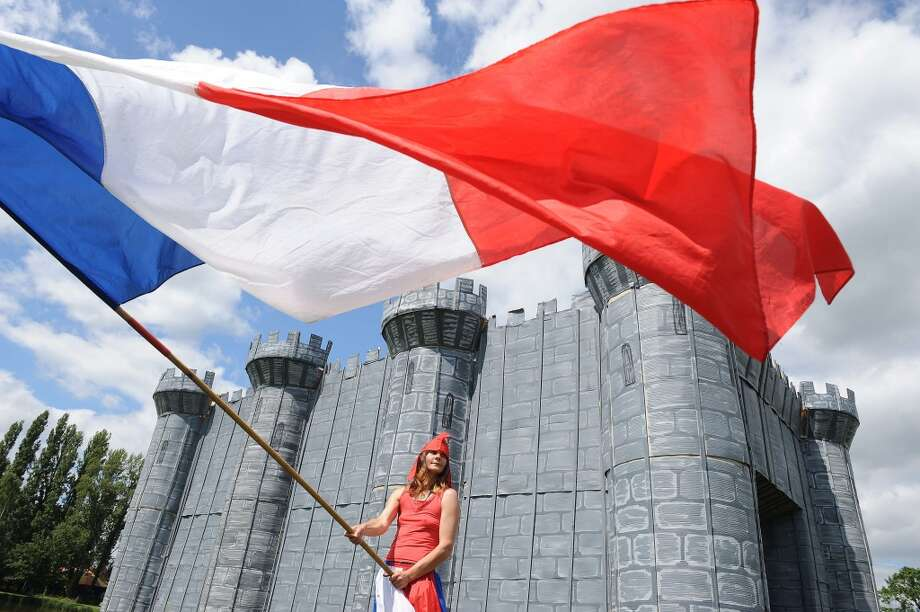 A villager dressed as Marianne, personification of the French Revolution, stands by a wooden and cardboard fortress and takes part in the commemorating of the storming of the Bastille during Bastille Day, in Lavaré, western France. In the dark night the villagers will take the Bastille and will set it on fire while dancing the carmagnole. AFP PHOTO / JEAN-FRANCOIS MONIERJEAN-FRANCOIS MONIER/AFP/Getty Images Photo: JEAN-FRANCOIS MONIER, AFP/Getty Images