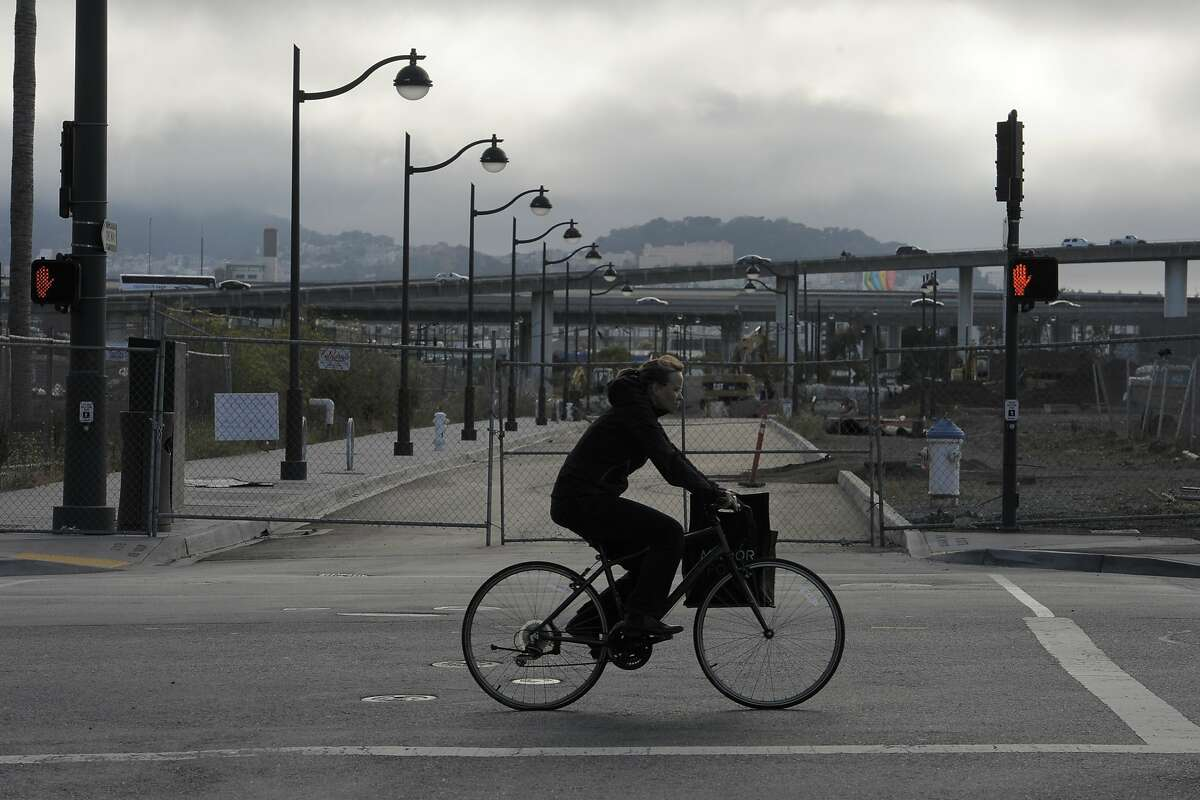 A woman rides her bike past a construction area on July 12, 2014 in the Mission Bay area of San Francisco, CA. Freeway-adjacent neighborhoods such as the Bayview have the unfortunate distinction of being the most polluted in San Francisco; they are also seeing the biggest amount of construction.
