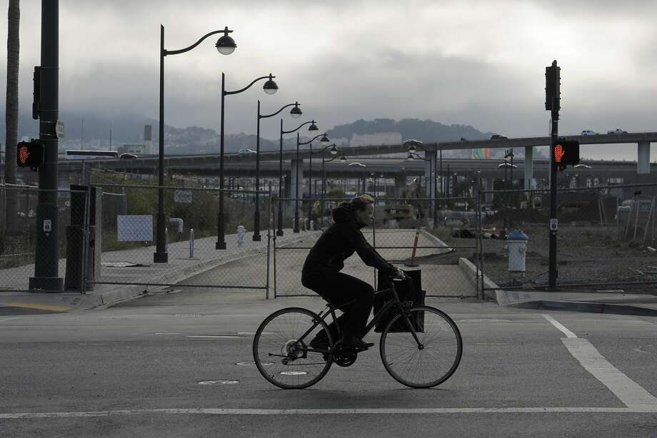 A bicyclist pedals past a construction site next to freeways in the Mission Bay neighborhood. Photo: Craig Hudson, The Chronicle