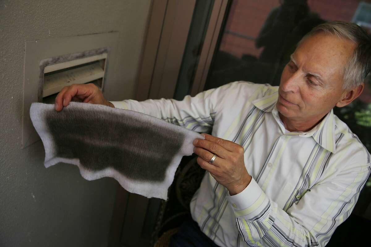 Joe Walseth of San Francisco removes a filter, which is typically used to control allergies, that he places on the outside of a vent on his balcony on Monday, July 14, 2014 in San Francisco, Calif.