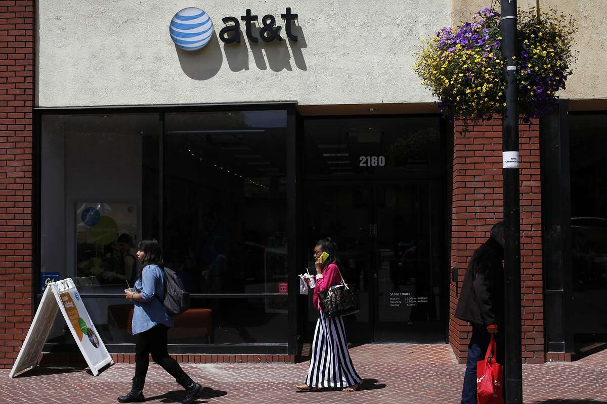 People walk past the AT&T store July 10, 2014 in Berkeley, Calif. Cell phone companies may be required to place a sticker on phones warning users of the risk of brain cancer, according to an ordinance Berkeley is considering.