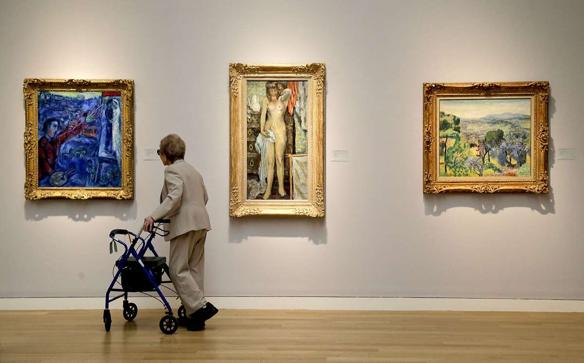 FILE - In this May 2, 2014 file photo, a woman browses various impressionistic paintings during a preview exhibition for Sotheby's Spring Evening Sale of impressionistic and modern art, in New York. EBay Inc. has partnered with Sotheby's to offer a new live auction feature on eBay's Web site and real-time bidding for auctions that are taking place at Sotheby's headquarters in New York. (AP Photo/Julie Jacobson, File)