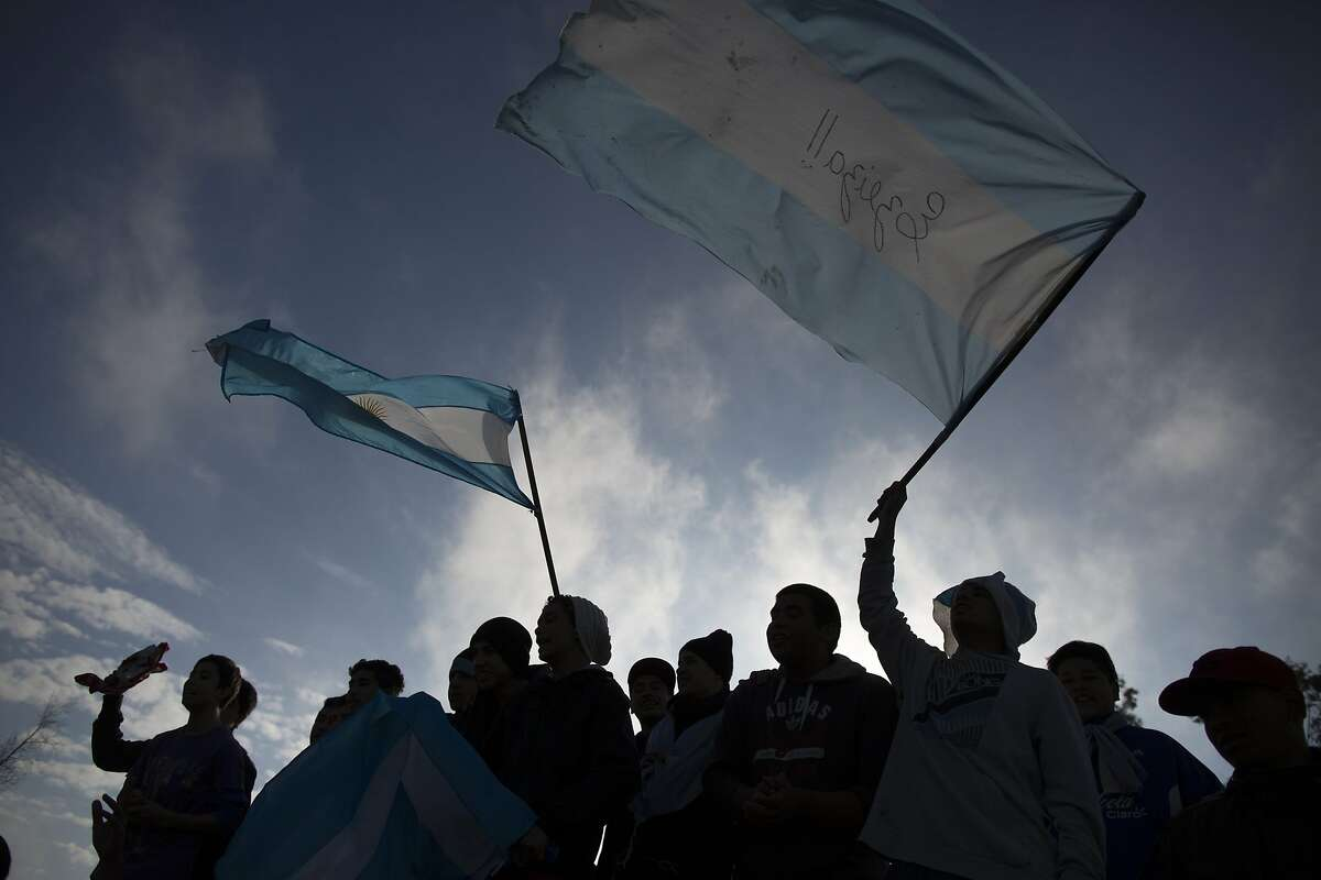 Argentina soccer fans wave flags as they wait for the arrival of Argentina's team to the airport in Buenos Aires, Argentina, Monday, July 14, 2014. Fans came out to welcome home Argentina's team after it was defeated 1-0 by Germany at the the Brazil World Cup final match on Sunday. (AP Photo/Ivan Fernandez)