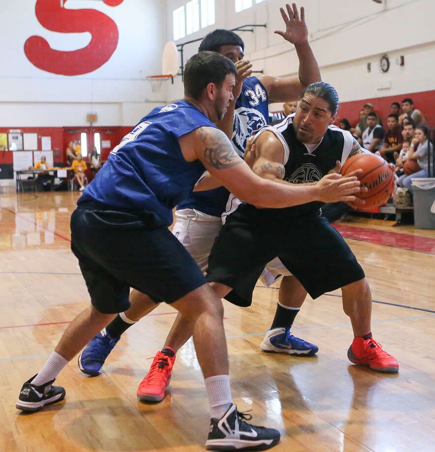 """1996 team member Eric """"Turtle"""" Trinidad, from right, looks for a way around Victor Mancha and Justin Rodriguez with the 2006 team, during the Sunday's Harlandale Alumni Basketball Tourney. The match featured 15 mens teams and five womens teams. Photo: Photos By Marvin Pfeiffer / Southside Reporter / Express-News 2014"""