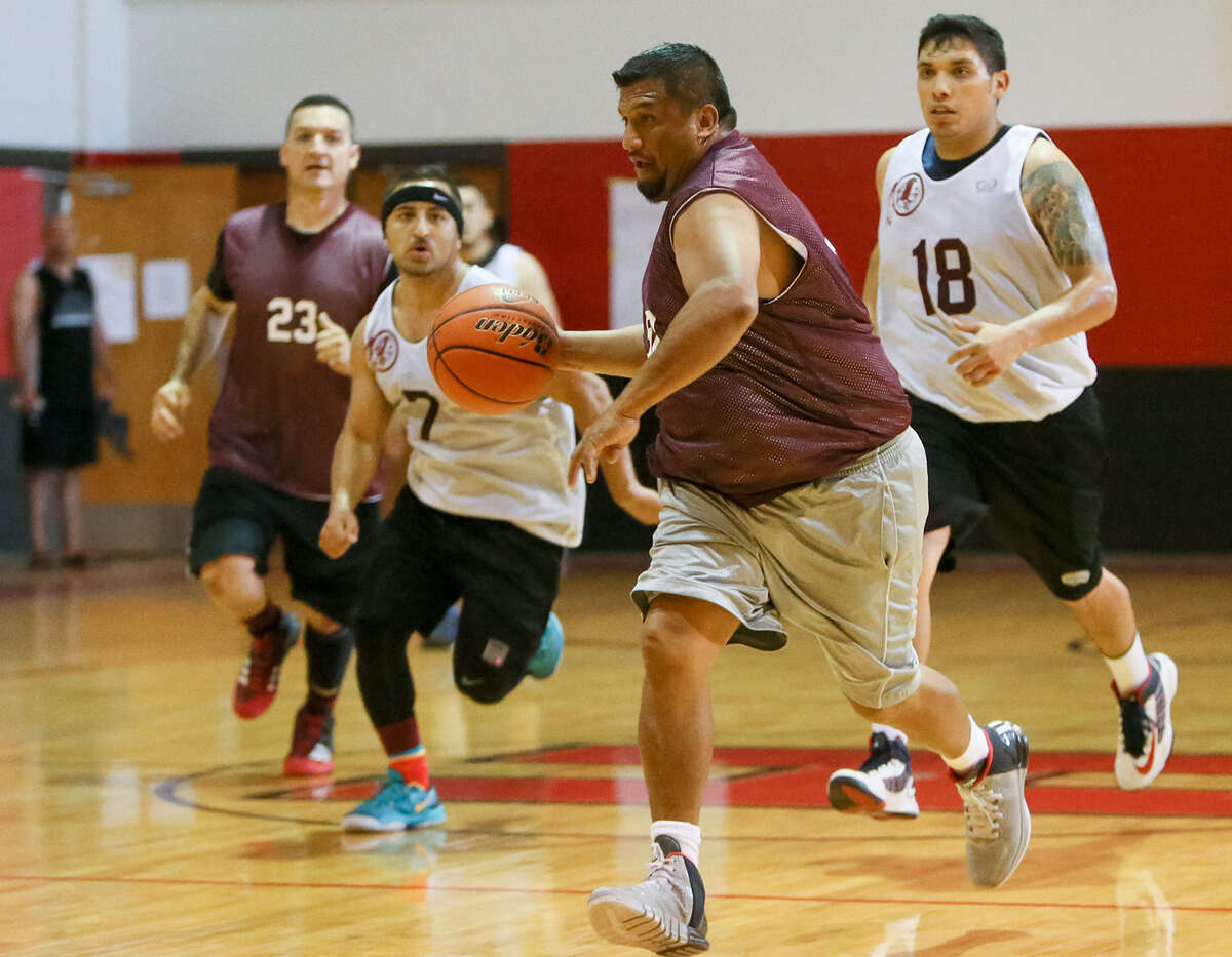 Salvador Dominguez, front, with the school's'80s team brings the ball upcourt as Diego Martinez, from left, Angel Sanchez and Mike Zapata, playing for the 2004 team, follow during Sunday's 2014 Harlandale Alumni Basketball Tourney at Harlandale Middle School. The three-day tournament is now in its ninth year.