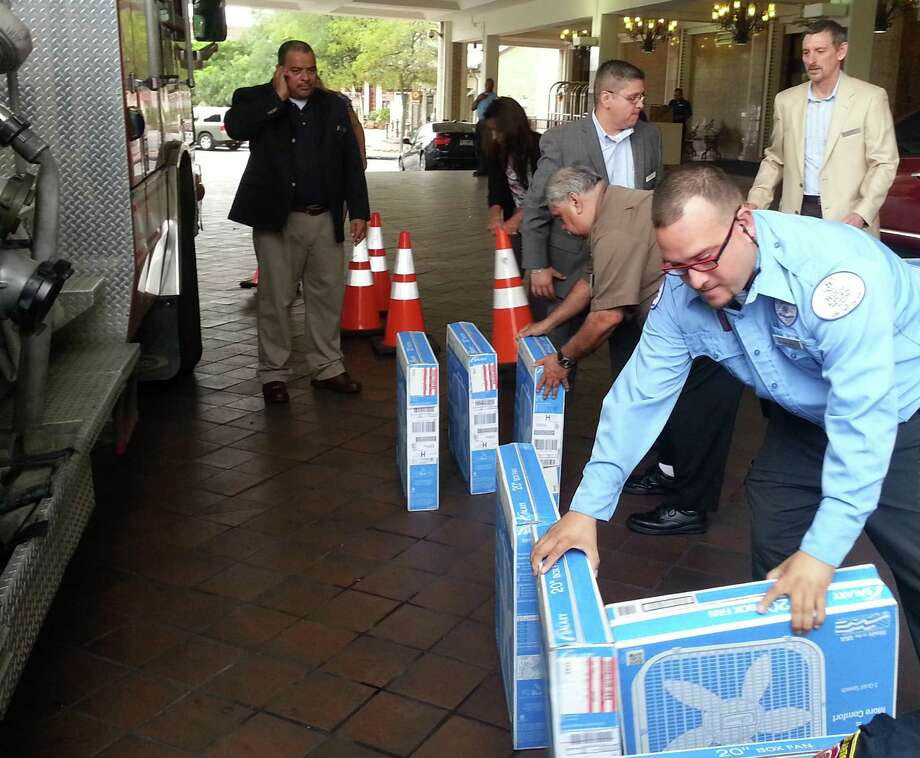 Hilton Palacio Del Rio security guard Ray Guillen (front) and Human Resources Manager Robert Chapa (center) organize fans donated by hotel employees for Project Cool as Housekeeping Director Ramon Garcia (far left) looks on. Photo: Jeremy Gerlach, Southside Reporter