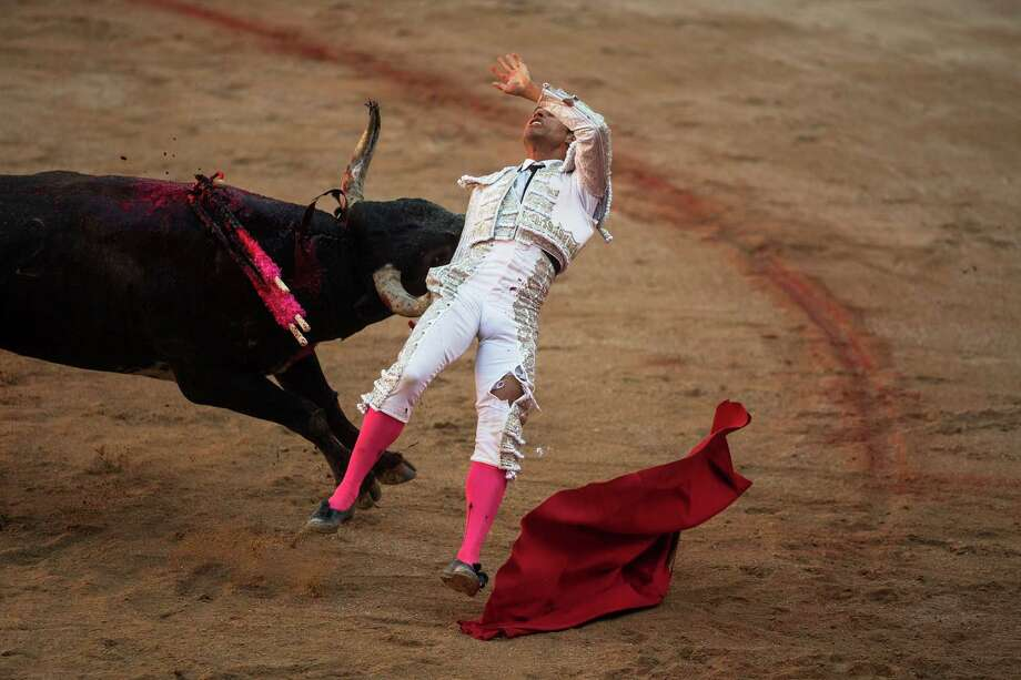 Colombian bullfighter Luis Bolivar is tossed by a Miura ranch fighting bull after he nailed a sword in the back of the bull, during a bullfight of the San Fermin festival in Pamplona, Spain, Monday, July 14, 2014. Photo: Andres Kudacki, Associated Press / AP