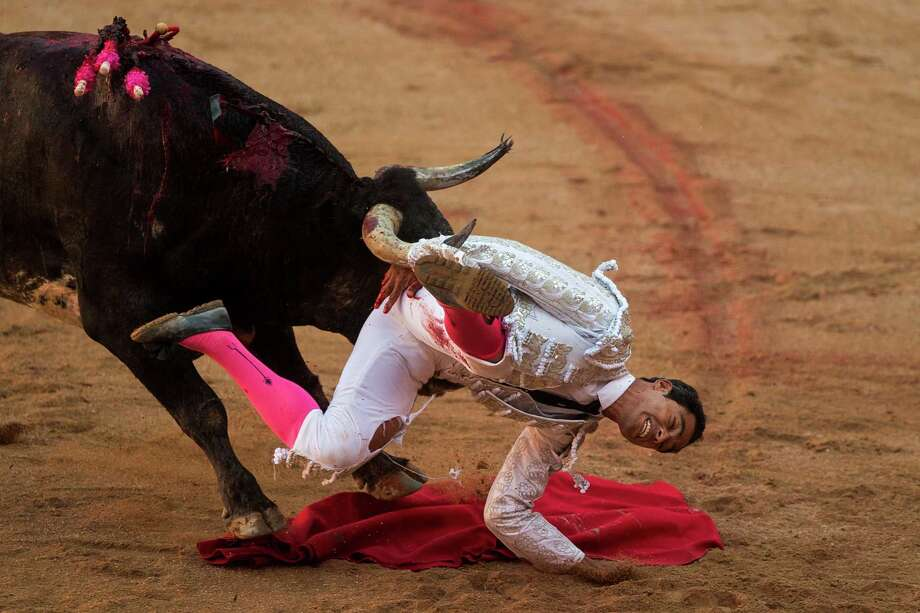 Colombian bullfighter Luis Bolivar is tossed by a Miura ranch fighting bull after he nailed a sword in the back of the bull, during a bullfight of the San Fermin festival in Pamplona, Spain, Monday, July 14, 2014. Revelers from around the world arrive to Pamplona every year to take part in some of the eight days of the running of the bulls.  Photo: Andres Kudacki, Associated Press / AP