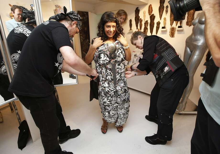 "Artist and activist Linda Stein (right) and her personal assistant Henry Galarza help Rinku Sen into a wearable piece of art in Stein's New York gallery. ""It's like putting on a whole new persona,"" Sen said. Photo: Kathy Willens, Associated Press"