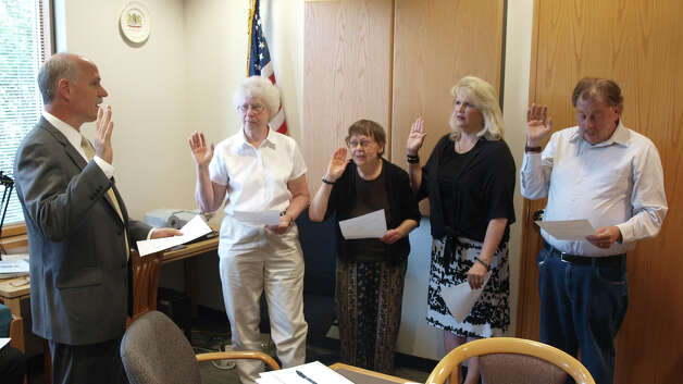 Board President Christopher Aldrich, left, swears in four members of the Guilderland Library?s Board of Trustees on July 10. From left, Barbara Fraterrigo, Carolyn Williams, Karen Carpenter Palumbo and Robert Feller take the oath. Williams and Palumbo are new to the board; Fraterrigo and Feller are incumbents. (Submitted by Mark Curiale)