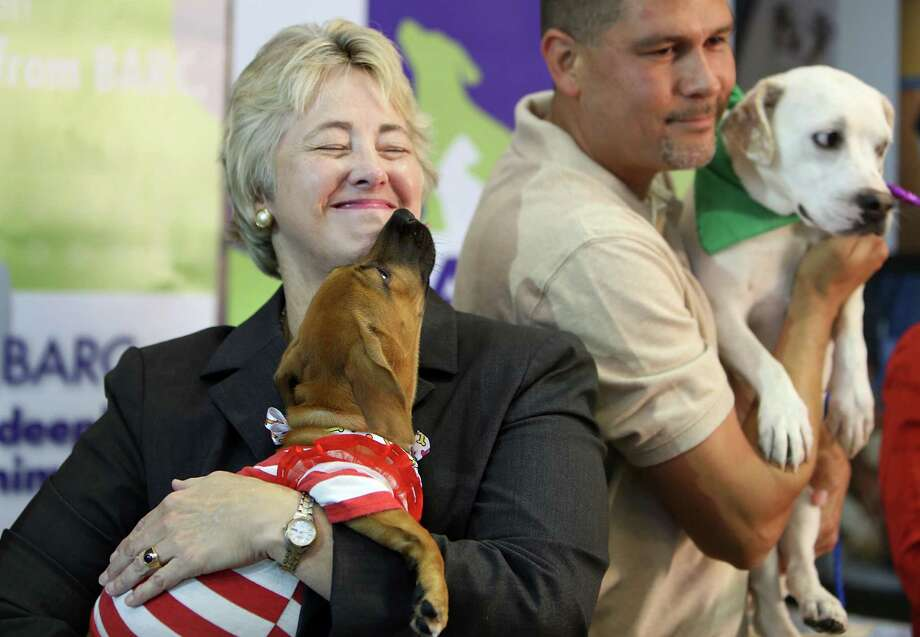 Houston Mayor Annise Parker smiles while embracing a dog at BARC after a press conference announcing the  progress of BARC's new adoption center and to highlight the shelter's major accomplishments on July 14, 2014, in Houston, Tx. Photo: Mayra Beltran, Houston Chronicle / © 2014 Houston Chronicle