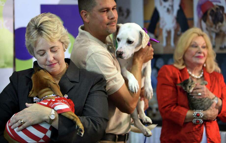 Houston Mayor Annise Parker embraces a dog at BARC after a press conference announcing the  progress of BARC's new adoption center and to highlight the shelter's major accomplishments on July 14, 2014, in Houston, Tx. Photo: Mayra Beltran, Houston Chronicle / © 2014 Houston Chronicle