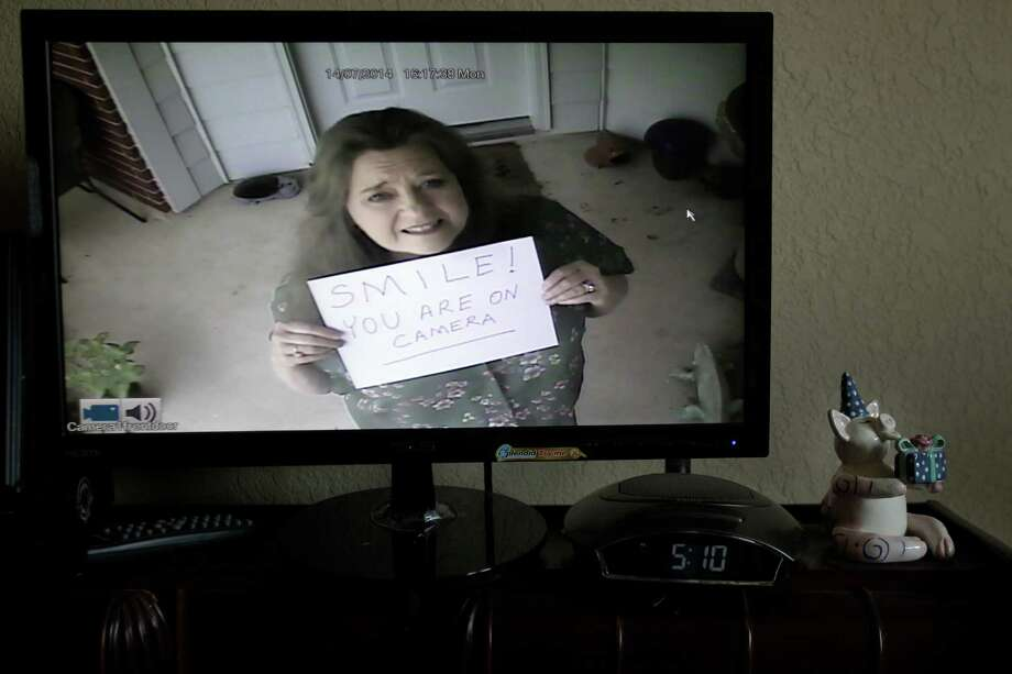 Judy Clark attempts to prevent AC unit thefts in her home by putting a sign on her unit alerting potential thieves that they're on camera. Photo: Mayra Beltran, Staff / © 2014 Houston Chronicle