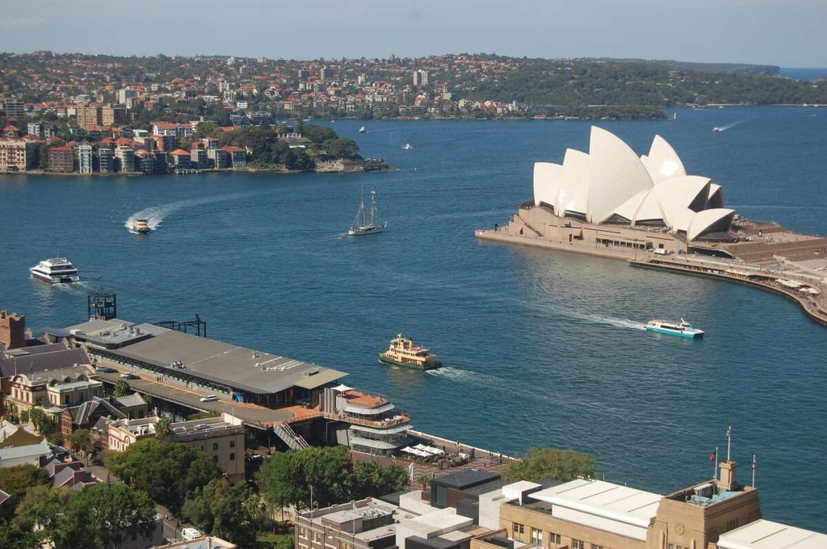 With its sail-inspired tile roofs, the iconic Sydney Opera House stands as the center of bustling Sydney Harbour.