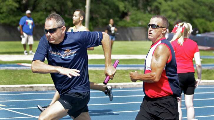 Jerry Krimbill, left, of San Antonio takes the handoff from Pete Dodd during the 4x100 meter relay during the Transplant Games at Rice University Monday. Krimbill was a kidney donor in 2009. Dodd is a heart transplant recipient.