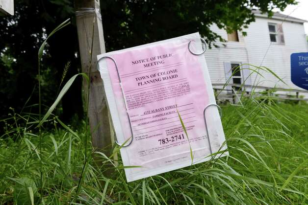 notice of public meeting is placed in front of a derelict property at 4232 Albany Street Monday afternoon, July 14, 2014, in Colonie, N.Y. The owner is proposing to use this land to park more than 200 cars as a staging area for a dealership. (Will Waldron/Times Union) Photo: WW / 00027788A