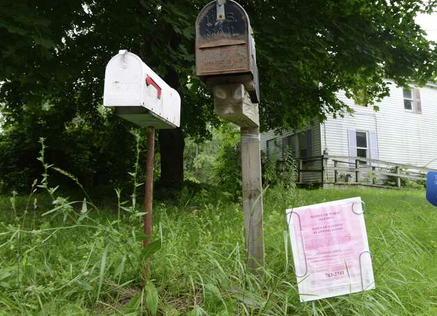 notice of public meeting is placed outside of a derelict property at 4232 Albany Street Monday afternoon, July 14, 2014, in Colonie, N.Y. The owner is proposing to use this land to park more than 200 cars as a staging area for a dealership. (Will Waldron/Times Union) Photo: WW / 00027788A