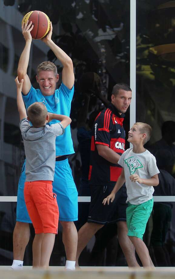 Germany's Bastian Schweinsteiger, left, plays basketball with kids as Lukas Podolski, wearing Brazil's Flamengo soccer jersey, walks behind at the Sheraton Hotel, one day after Germany won the World Cup in Rio de Janeiro, Brazil, Monday, July 14, 2014. (AP Photo) Photo: Associated Press