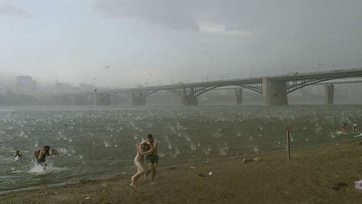 Hailstone barrage:In this photo taken on a smartphone, Russians run for shelter as large hailstones rain down on them on a beach of the Ob River in Novosibirsk, Siberia. Authorities said two young girls died in Bredsk, not far from Novosibirsk, when a tree fell on their tent during the storm.