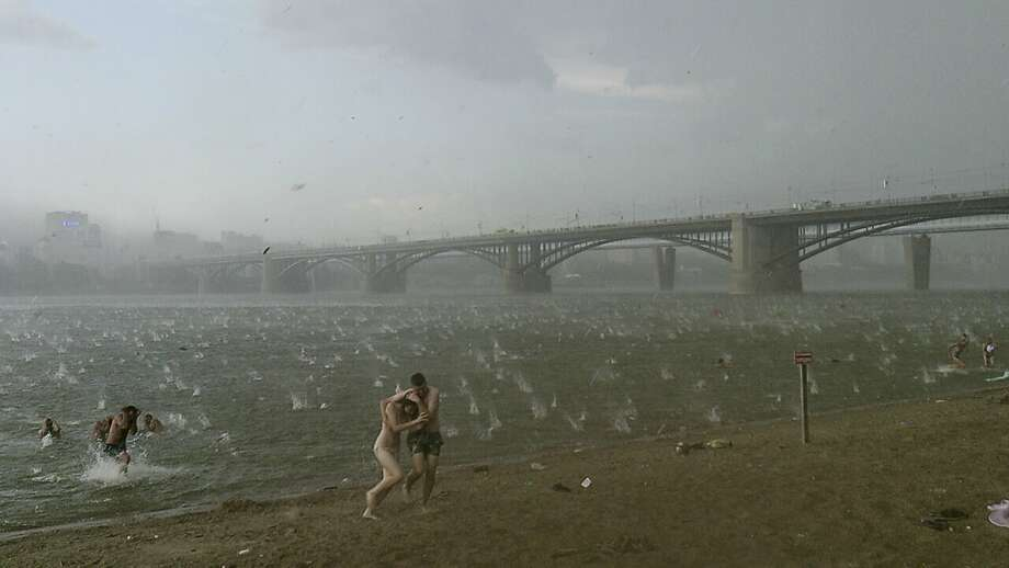 Hailstone barrage:In this photo taken on a smartphone, Russians run for shelter as large hailstones rain down on them 