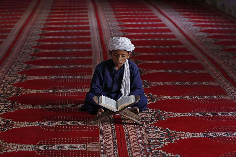 An Afghan boy reads the Quran during the Muslim holy month of Ramadan at a mosque in Kandahar, Afghanistan, Monday, July 14, 2014. For believers, Ramadan is meant to be a time of reflection and worship, remembering the hardships of others and being charitable. (AP Photo/Allauddin Khan) Photo: Allauddin Khan, Associated Press