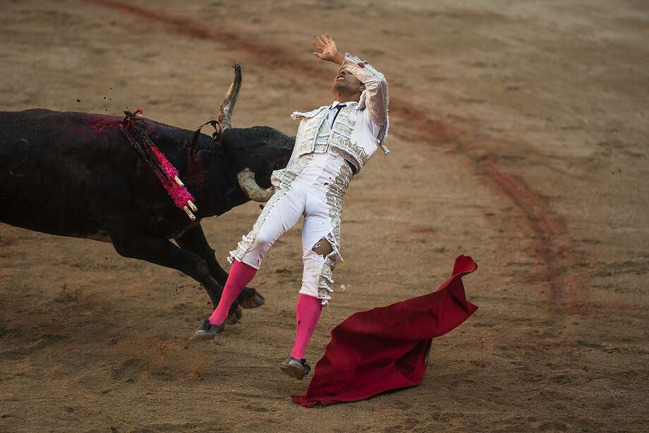 Colombian bullfighter Luis Bolivar is tossed by a Miura ranch fighting bull after he nailed a sword in the back of the bull, during a bullfight of the San Fermin festival in Pamplona, Spain, Monday, July 14, 2014. Revelers from around the world arrive to Pamplona every year to take part in some of the eight days of the running of the bulls. (AP Photo/Andres Kudacki) Photo: Andres Kudacki, Associated Press