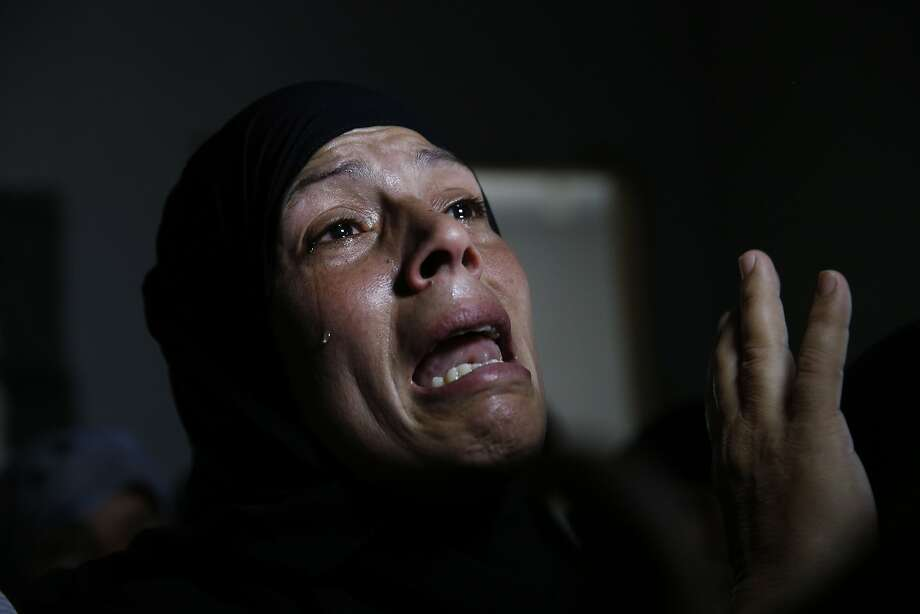 A Palestinian mourner cries in a house after the bodies of Mousa Abu Muamer, 56, and his son Saddam, 27, who were killed in an overnight Israeli missile strike at their house in the outskirts of the town of Khan Younis, southern Gaza Strip, were brought in for their funeral, Monday, July 14, 2014. Saddam's wife, Hanadi, 27, was also killed in the attack. (AP Photo/Lefteris Pitarakis) Photo: Lefteris Pitarakis, Associated Press