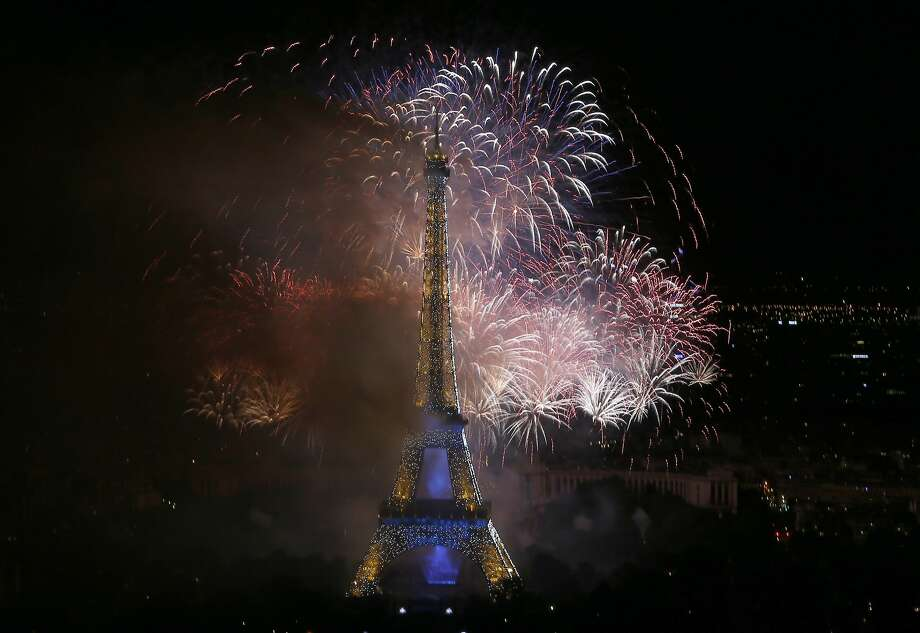 Bastille Day fireworks explode over the Seine river next to the Eiffel Tower in Paris Monday night, July 14, 2014. Bastille Day commemorates the storming by Parisians of the Bastille prison on July 14, 1789, setting off the French Revolution that toppled King Louis XVI and put an end to monarchy.(AP Photo/Jacques Brinon) Photo: Jacques Brinon, Associated Press