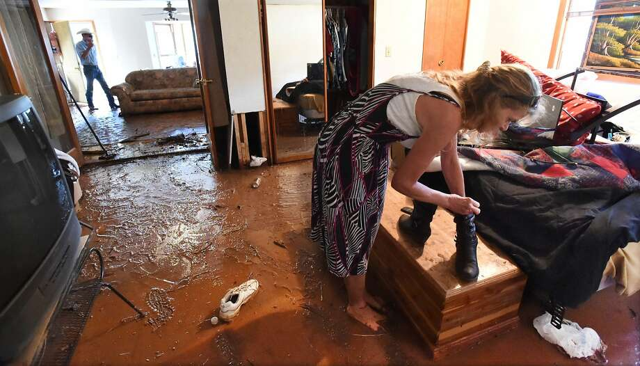 Dottie Goeller finds a pair of dry and clean boots to wear while wading through mud on the floor of the house where she is living in Green Mountain Falls, Colo., on Monday, July 14, 2014. Last year, the same home was flooded during the summer rains.  (AP Photo/The Colorado Springs Gazette, Jerilee Bennett) MAGS OUT Photo: Jerilee Bennett, Associated Press