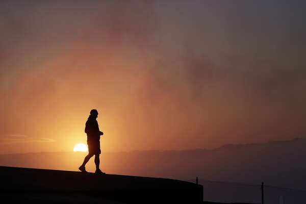 Russell Brown, of Los Altos, Calif., watches the sunrise from a a hill in the Marin Headlands on Monday, July 14, 2014, in San Francisco. (AP Photo/Marcio Jose Sanchez)
