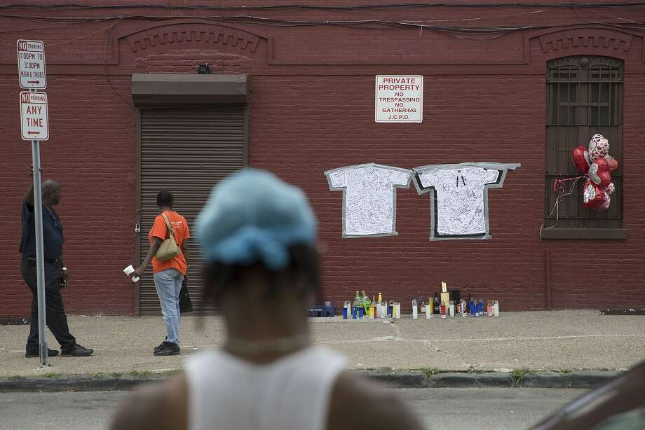 Pedestrians stand near a memorial to Lawrence Campbell, who allegedly shot and killed 23-year-old Jersey City police officer Melvin Santiago, Monday, July 14, 2014, in Jersey City, N.J. Campbell was also killed at the scene after police officers returned fire. (AP Photo/John Minchillo) Photo: John Minchillo, Associated Press