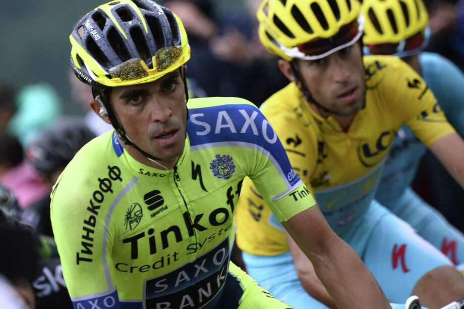 Spain's Alberto Contador (L) and Italy's Vincenzo Nibali wearing the overall leader's yellow jersey ride in the pack during the 161 km eighth stage of the 101st edition of the Tour de France cycling race on July 12, 2014 between Tomblaine and Gerardmer La Mauselaine, eastern France.  AFP PHOTO / LIONEL BONAVENTURELIONEL BONAVENTURE/AFP/Getty Images ORG XMIT: 496131327 Photo: LIONEL BONAVENTURE / AFP