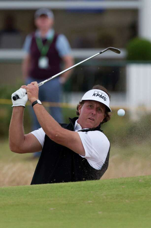 Phil Mickelson of the US plays out of a bunker by the 2nd green during a practice round at Royal Liverpool Golf Club prior to the start of the British Open Golf Championship, in Hoylake, England, Monday, July 14, 2014. The 2014 British Open Championship starts on Thursday, July 17. (AP Photo/Jon Super) ORG XMIT: MJS129 Photo: Jon Super / AP