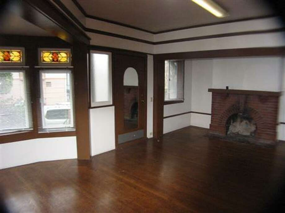 The original living room, with brick fireplace. Photo: MLS