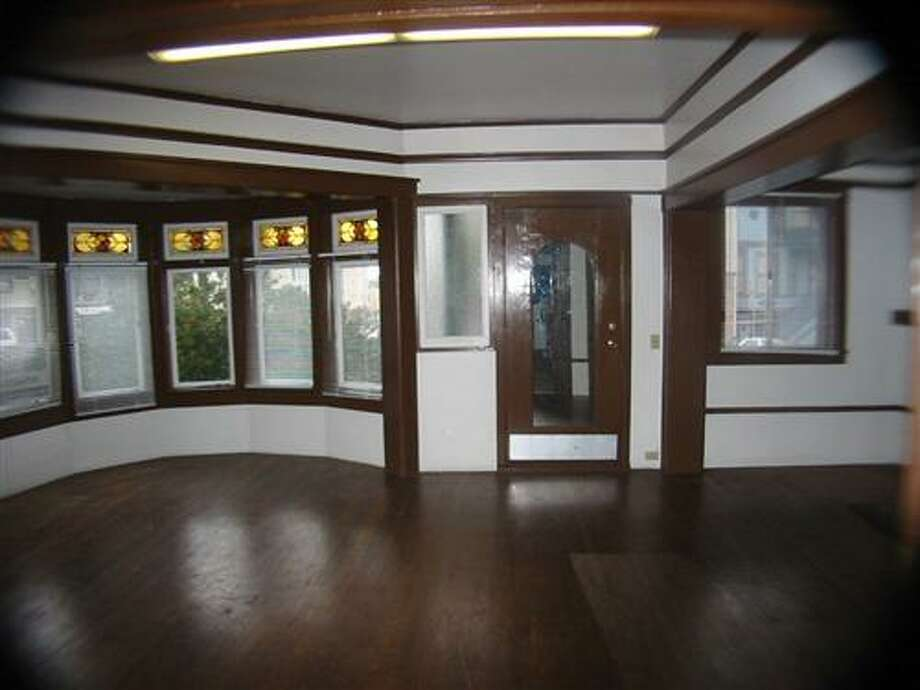 The original entertaining space with unpainted wood trim. Photo: MLS