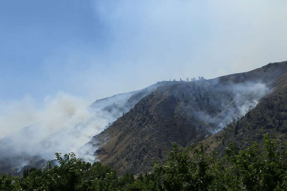 Smoke rises from the area of a wildfire near Entiat, Wash., Friday, July 11, 2014. Several hundred firefighters worked Friday to contain the fire that has burned grass and brush across nearly 30 square miles in central Washington.  Photo: Rachel La Corte, Associated Press