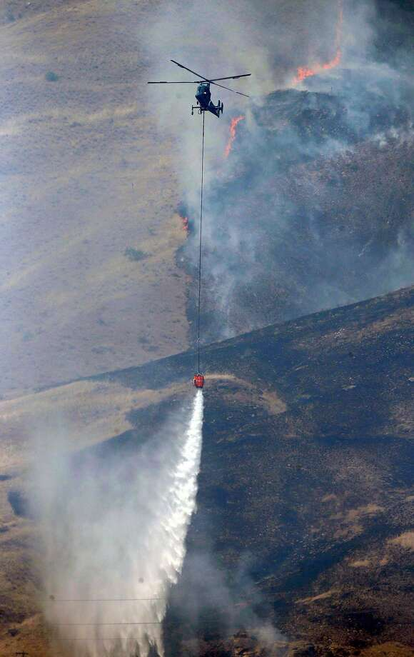 Helicopters dump water from the Columbia River onto the Mills Canyon Fire near Entiat in Chelan County, Wash., on July 10 as hot, dry weather blankets the state and has fire crews on alert.  Photo: Bettina Hansen, McClatchy-Tribune News Service